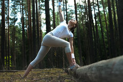 Corredor de la mujer que estira después del entrenamiento corriente en bosque y que mira al cielo Imagen de archivo libre de regalías