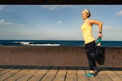 Corredor de la mujer que estira en la playa en día de verano soleado fotos de archivo libres de regalías