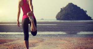 Corredor de la mujer que estira las piernas antes de correr imagen de archivo libre de regalías