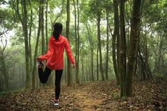 Corredor de la mujer que estira las piernas antes de funcionamiento en bosque foto de archivo libre de regalías