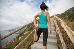 Corredor de la mujer que estira las piernas en rastro de montaña Fotos de archivo libres de regalías