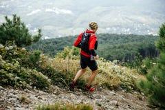 Corredor de maratona masculino do atleta que corre com as montanhas ao longo da fuga Fotos de Stock Royalty Free