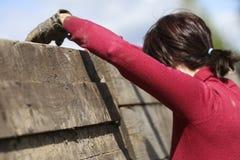 Corredor de raça enlameado do obstáculo na ação Corrida da lama foto de stock