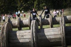 Corredor de raça enlameado do obstáculo na ação Corrida da lama imagem de stock