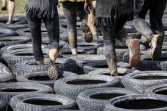 Corredor de raça enlameado do obstáculo na ação Corrida da lama foto de stock royalty free