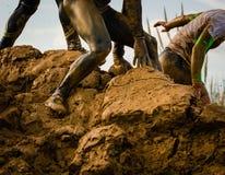 Corredor de raza fangoso de obstáculo en la acción Funcionamiento del fango imagenes de archivo