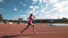 Corredor de vallas femenino profesional durante el entrenamiento metrajes