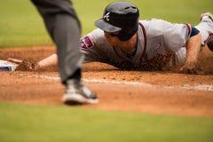 Corredor del Atlanta Braves que resbala dentro de la primera base Imágenes de archivo libres de regalías