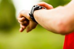 Corredor del campo a través que mira el reloj del deporte Imagenes de archivo