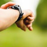 Corredor del campo a través que mira el reloj del deporte Imagen de archivo