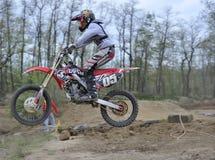 Corredor del motocrós que salta sobre una pequeña colina Imagen de archivo