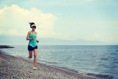 Corredor del rastro de la mujer de la aptitud que corre en la playa Foto de archivo libre de regalías