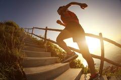 Corredor del rastro de la mujer de la aptitud que corre en las escaleras de la montaña de la playa Fotografía de archivo