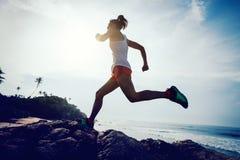 Corredor del rastro de la mujer que corre al top de la montaña rocosa fotografía de archivo libre de regalías