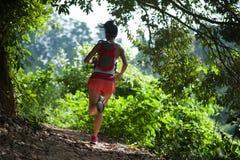 Corredor del rastro de la mujer que corre en rastro tropical del bosque imagenes de archivo