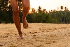 Corredor descalço na praia no por do sol foto de stock