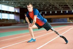 Corredor discapacitado que estira en estadio imagenes de archivo