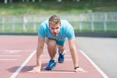 Corredor do homem na posição de começo no estádio Corredor na pose do começo em superfície running Exterior corrido homem na pist Imagem de Stock Royalty Free