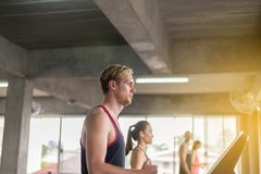 Corredor do homem nas escadas rolantes que fazem o cardio- treinamento em um gym, conceito saudável do estilo de vida imagem de stock royalty free