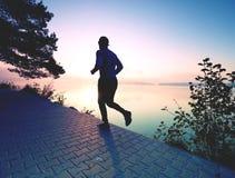 Corredor do homem no pavimento da costa do lago durante o nascer do sol ou o por do sol foto de stock