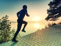 Corredor do homem no pavimento da costa do lago durante o nascer do sol ou o por do sol fotos de stock