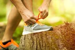 Corredor do homem novo que amarra suas sapatas no parque Fotografia de Stock Royalty Free