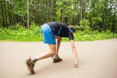Corredor do homem novo que prepara-se para uma corrida na trilha fotos de stock