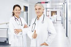 Corredor do hospital do doutor do homem do doutor da mulher imagens de stock