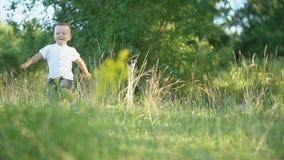Corredor do menino através do gramado vídeos de arquivo