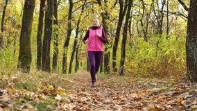 Corredor do movimento lento - corredor da mulher que movimenta-se no trajeto de floresta do outono Treinamento running da fuga fê filme