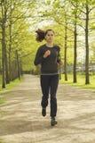 Corredor en la acción Mujer que activa que corre en parque en hermoso Fotografía de archivo