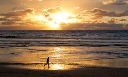 Corredor en la playa en la puesta del sol Foto de archivo