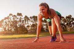 Corredor fêmea em uma trilha do atletismo fotografia de stock