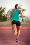 Corredor fêmea em uma trilha do atletismo Imagens de Stock
