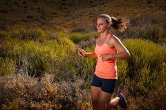 Corredor fêmea louro da fuga que corre com uma paisagem da montanha Fotografia de Stock