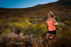 Corredor fêmea louro da fuga que corre com uma paisagem da montanha Imagem de Stock