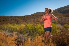 Corredor fêmea louro da fuga que corre com uma paisagem da montanha Imagens de Stock