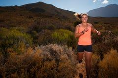 Corredor fêmea louro da fuga que corre com uma paisagem da montanha Imagens de Stock Royalty Free