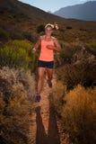 Corredor fêmea louro da fuga que corre com uma paisagem da montanha Fotografia de Stock Royalty Free