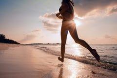 Corredor fêmea na praia na silhueta do por do sol no ar mais distante fotografia de stock