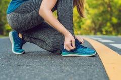 Corredor fêmea que amarra suas sapatas que preparam-se para movimentar-se fora você fotos de stock