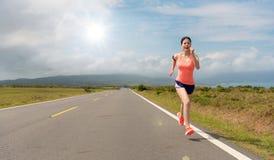 Corredor feliz da mulher no movimento da estrada asfaltada fotografia de stock