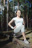 Corredor feliz de la mujer que hace el entrenamiento que estira hacia fuera al aire libre en bosque Imagen de archivo libre de regalías