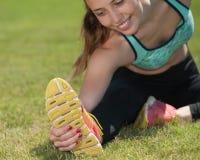 Corredor femenino atractivo en estiramiento de los corredores de vallas Fotografía de archivo