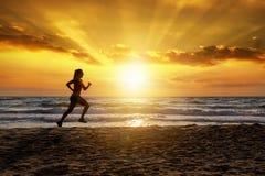 Corredor femenino en una playa en el tiempo de la puesta del sol fotos de archivo libres de regalías