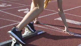 Corredor femenino experimentado que sale de los bloques el comenzar, entrenamiento activo en el lento-MES almacen de video