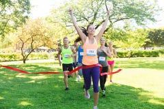 Corredor femenino joven feliz que gana en final de la raza Fotos de archivo