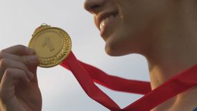 Corredor femenino joven que gana la competencia, la medalla sonriente y que se besa de la muchacha de oro metrajes