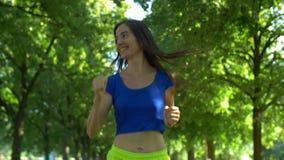 Corredor femenino que activa durante entrenamiento al aire libre en parque almacen de video