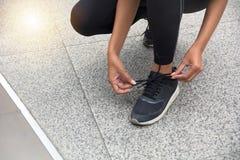 Corredor femenino que ata los zapatos que se preparan para un funcionamiento imagenes de archivo